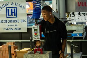 A STUDENT SMILES WHILE TAKING PART IN THE SKILLED TRADE WORKSHOP AT THE SACHSE CONSTRUCTION ACADEMY.