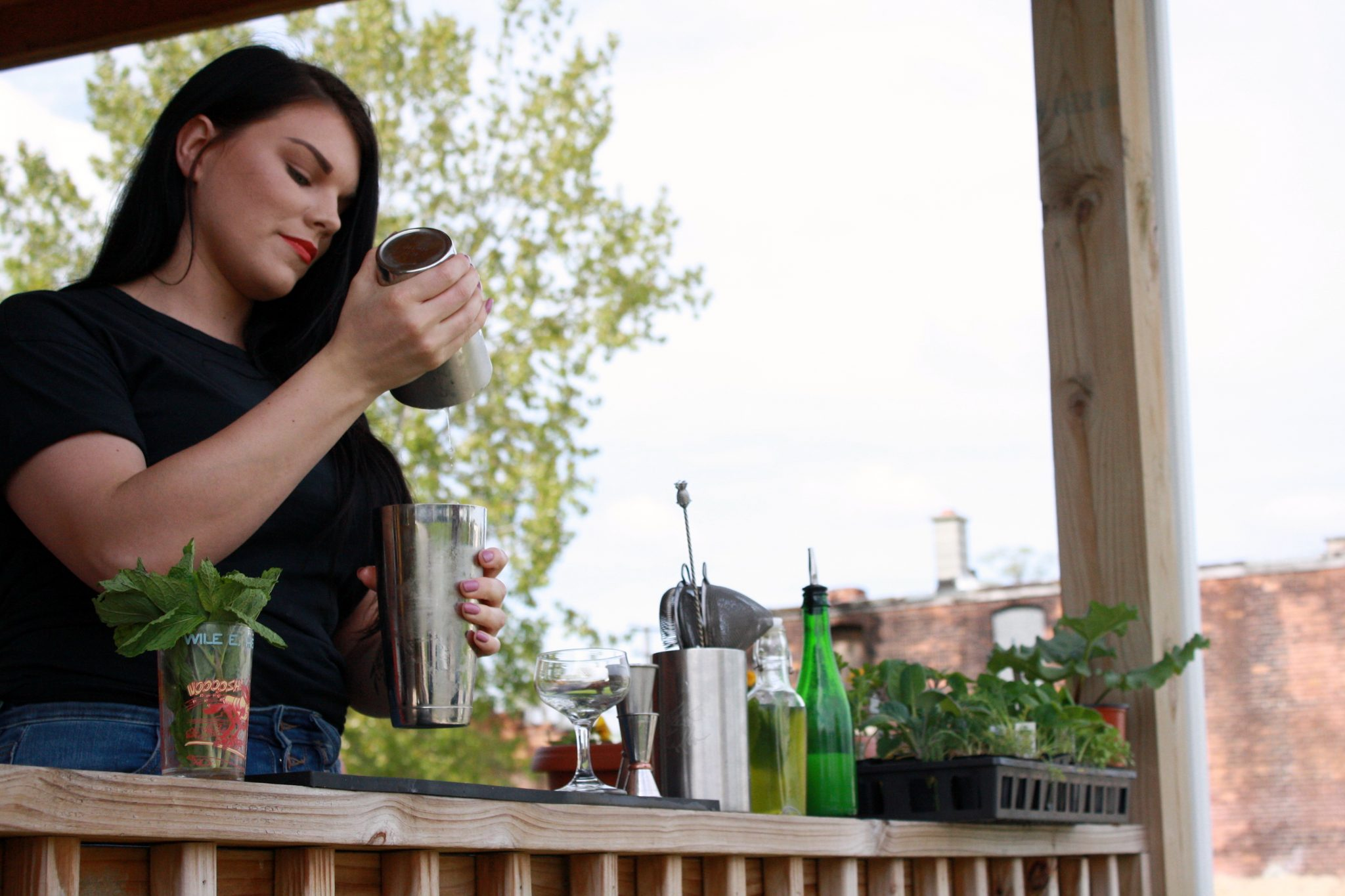 BARTENDER ALLISON EVERITT SHAKING A COCKTAIL ON THE FRONT PORCH OF HER DETROIT HOME