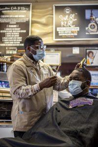 A BARBER CUTS HAIR INSIDE EXECTUIVE CUTS. PHOTO JOHN BOZICK