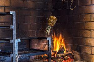 A PINEAPPLE ABOVE A WOOD BURNING FIRE INSIDE OAK & REEL. PHOTO JOHN BOZICK