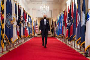 how do you rate biden's first 100 days? // biden walking down a hall with a mask // PRESIDENT JOE BIDEN BEFORE DELIVERING COVID-19 REMARKS ON MARCH 11, 2021. OFFICIAL WHITE HOUSE PHOTO BY ADAM SCHULTZ